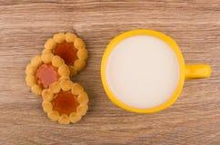 3 печенья с вареньем и чашкой молока на таблице Стоковые Фото