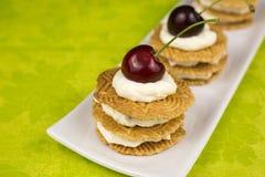 Печенья с взбитыми сливк и вишней Стоковые Изображения RF