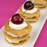 Печенья с взбитыми сливк и вишней Стоковые Фото