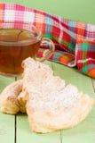 2 печенья слойки с чашкой чаю на зеленой деревянной предпосылке Стоковые Изображения
