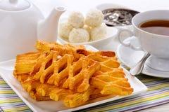 Печенья слойки, чашка чаю и чайник на белом деревянном столе Стоковое фото RF
