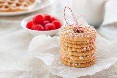 Печенья с падениями сахара и красная лента на белой плите с полениками на предпосылке на linen ткани Стоковое Изображение