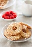 Печенья с сахаром падают на белую плиту с полениками на предпосылке на linen ткани Стоковое Фото