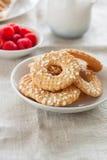Печенья с сахаром падают на белую плиту с полениками на предпосылке на linen ткани Стоковое Изображение