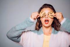 Печенья так потеха и простые Милая девушка покрывая глаза с печеньями Милая девушка имея потеху с печеньями bakersfield стоковое фото