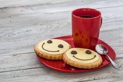 Печенья улыбки на красной плите с чашкой кофе, деревянной предпосылкой, едой Стоковые Фото