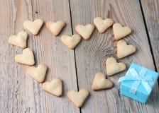 Печенья формы сердца с голубой подарочной коробкой на деревянном столе для Val Стоковое Изображение RF