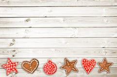 Печенья хлеба имбиря и орнаменты рождества на белой деревянной предпосылке планок Стоковое фото RF
