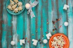 Печенья для рождества на 2 покрашенных плитах и горящем candl Стоковое Изображение