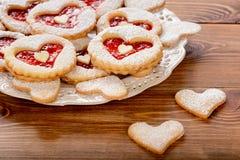 Печенья Shortbread в форме сердца с вареньем клубники на деревянном столе Стоковые Фото