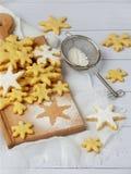 Печенья shortbread рождества в форме снежинок брызгая сахар на белой предпосылке Стоковые Изображения