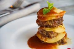 Печень икры с яблоками клала слои с соусом на белую плиту Стоковая Фотография RF