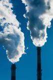 2 печной трубы с драматическими облаками дыма. Стоковые Фото