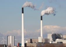 Печные трубы фабрики с облаками и малыми ветрянками Стоковая Фотография