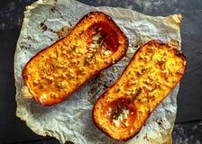 Печь испекла половины сквоша butternut с тимианом, розмариновым маслом и сыр фета заморосил с оливковым маслом Стоковые Фото