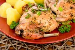 Печь испекла кролика с картошками на красной плите на деревянном столе Стоковые Изображения RF