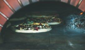 Печь пиццы с сыром и мясом в печи пиццы деревянной стоковые изображения