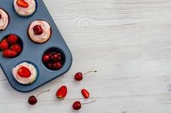 Печь поднос с плодом и пирожными на белой деревянной предпосылке стоковые фото