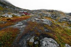 Пешая тропа водя к удаленной красной деревянной кабине в горах на Lofoten в Норвегии стоковые фотографии rf