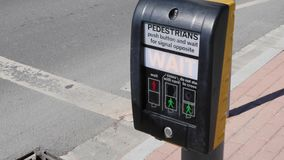Пешеход отжимая кнопку ожидания для того чтобы пересечь улицу безопасно Обеспечение безопасности на дорогах ( видеоматериал
