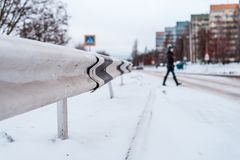 Пешеход пересекает дорогу в зиме в городе на покрытой снег дороге, трассировки колес на снеге в городе Стоковое фото RF