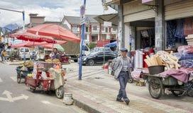 Пешеход проходит поставщика еды с стойлом велосипеда на улице Lijiang Стоковое фото RF