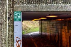 Пешеход и путь ciclyst под дорогой при ярлык говоря - пожалуйста наденьте ` t средний Позвольте ` s держать наши улицы чистый Стоковое фото RF