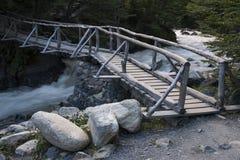 Пешеходный деревянный мост над потоком горы Стоковое Фото