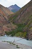 Пешеходный мост через реку в горах Тянь-Шань Стоковое Изображение RF