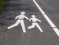 Пешеходный логотип на гудронированном шоссе Стоковые Фото