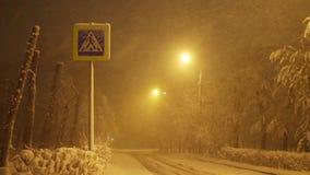 Пешеходный переход знака, снежностей на пустой дороге на ноче в городе сток-видео