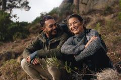 Пешие пары сидя на горной тропе Стоковая Фотография