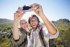 Пешие пары стоя на местности горы принимая selfie Стоковое Фото