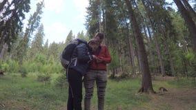 Пешие пары backpackers в лесе смотря gps составляют карту использующ на smartphone во время похода - видеоматериал