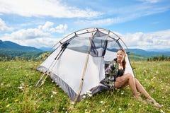 Пеший туризм женщины туристский в горной тропе, наслаждаясь утром лета солнечным в горах около шатра стоковое фото rf