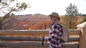 Пеший туризм женщины туристский к каньону Bryce гор красного песчаника предпосылки оранжевому стоковое фото
