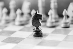 Пешка рыцаря шахмат на конце шахматной доски вверх черная белизна Стоковое Фото