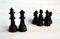 Пешки шахматных фигур стоят в толпе между королем и ферзем стоковое изображение
