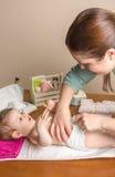 Пеленка матери изменяя прелестного младенца Стоковая Фотография