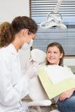 Педиатрический дантист говоря с маленькой девочкой в стуле дантистов Стоковое Изображение