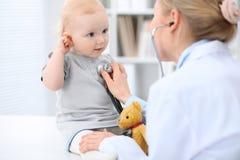 Педиатр позаботится о младенец в больнице Маленькая девочка рассматривает доктором с стетоскопом стоковое фото rf