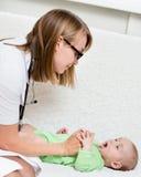 Педиатр рассматривает newborn младенца с шпателем Стоковые Фото