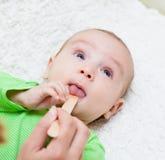 Педиатр рассматривает newborn младенца с шпателем стоковое фото