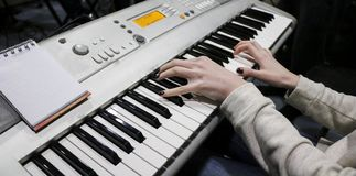 Пианист маленькой девочки играет электронный рояль с ее любимой музыкой Женские грациозно руки касаются ключам синтезатора c Стоковое Изображение