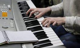 Пианист маленькой девочки играет электронный рояль с ее любимой музыкой Женские грациозно руки касаются ключам синтезатора c Стоковое фото RF