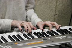 Пианист маленькой девочки играет электронный рояль с ее любимой музыкой Женские грациозно руки касаются ключам синтезатора c Стоковое Изображение RF