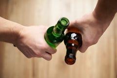 Пивные бутылки владением друзей Стоковые Фотографии RF