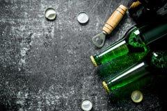 Пивные бутылки и консервооткрыватель стоковая фотография rf