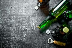 Пивные бутылки и консервооткрыватель стоковая фотография