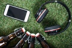 Пивные бутылки при smartphone и наушники лежа на зеленой траве Стоковые Фото